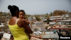 Ysamar Figueroa, y su hijo Saniel, observan el daño causado por el huracán María a su barrio en Canovanas, Puerto Rico. Sept. 26, 2017.