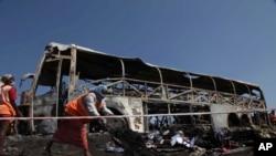 Para pekerja membersihkan puing-puing pasca kecelakaan bus yang menabrak pembatas jalan dan terbakar, di Mehabubnagar, Andhra Pradesh, India (30/10).