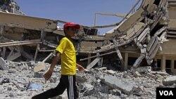 Seorang anak laki-laki Libya melewati gedung universitas di Zlitan yang hancur akibat serangan udara NATO (4/8).