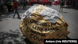 """Tulisan """"omnibus law lebih bahaya dari COVID"""" tampak di tengah demo buruh memprotes Undang-Undang Cipta Kerja, di Bandung, Jawa Barat, Selasa, 6 Oktober 2020. (Foto: Antara via Reuters)"""