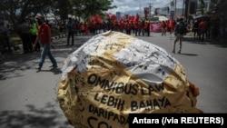 "Tulisan ""omnibus law lebih berbahaya dari COVID"" tampak di tengah demo buruh memprotes Undang-Undang Cipta Kerja, di Bandung, Jawa Barat, Selasa, 6 Oktober 2020. (Foto: Antara via Reuters)"