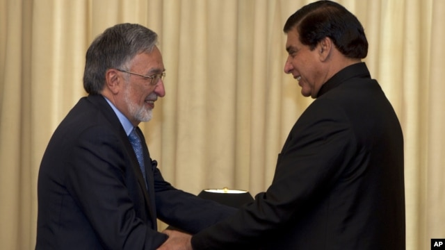 Afghan Foreign Minister Zalmay Rasoul, left, shakes hands with Pakistan's Prime Minister Raja Pervaiz Ashraf in Islamabad, Pakistan, November 30, 2012.
