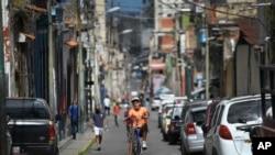 Un joven hace caballito en una bicicleta por las calles del barrio La Pastora de Caracas, Venezuela. Agosto 22, 2020.