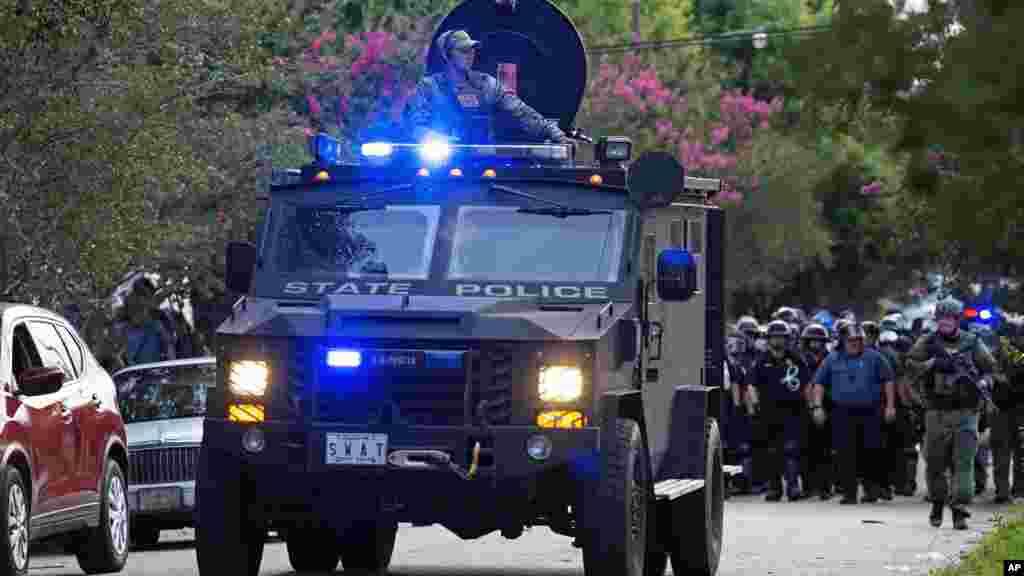 Un camion blindé de la police roule en tête d'une patrouille de policiers dans un quartier résidentiel à Baton Rouge.