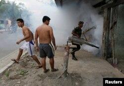 FILE - A Bolivian soldier fumigates a slum to prevent dengue in Villa Tunari in the Chapare region, some 310 km east of La Paz, October 10, 2014.