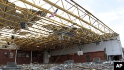 An American flag flies over the damaged gym at Henryville High School in Henryville, Indiana, March 3, 2012.