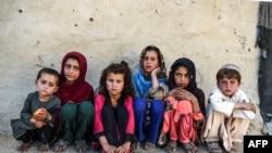 Anak-anak duduk di depan sebuah rumah di desa Deh Qubad di distrik Maiwand, Provinsi Kandahar, Afghanistan, 27 September 2020. (Foto: AFP)