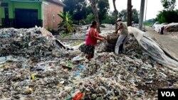 Supiati dan Saji mengangkut sampah plastik impor di pekarangan mereka di Mojokerto, Jawa Timur, untuk kemudian disortir dan dijual kembali (foto: Petrus Riski/VOA).