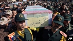 FILE - Civilians and armed forces members carry the flag-draped coffins of Iranian Revolutionary Guard Gen. Mohsen Ghajarian, foreground, and five soldiers who were killed in fighting in Syria, during their funeral outside the headquarters of the guard's ground forces, in Tehran, Iran, Feb. 6, 2016.