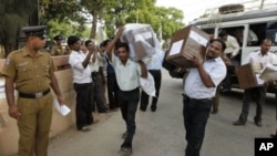 Police stand guard, left, as Sri Lankan polling officials carry ballot boxes to a counting center in Jaffna, Sri Lanka, July 23, 2011