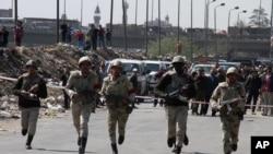 Polisi militer Mesir berlari menuju lokasi yang diserang oleh sekelompok orang bersenjata di Shubra al-Kheima di sebelah utara Kairo.