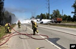Photo made available by the Chatham Emergency Services, GA., shows firefighters putting out a fire caused by a plane crash near the airport in Savannah, Ga., May 2, 2018.