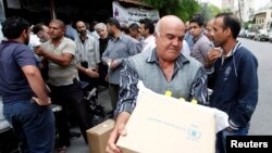 Para pengungsi Suriah menerima bantuan pangan PBB di Damaskus tahun lalu (foto: dok).