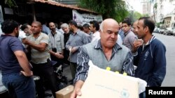 FILE - Displaced Syrians collect rations provided by the World Food Program in front of a distribution center in Damascus, Oct. 19, 2014.