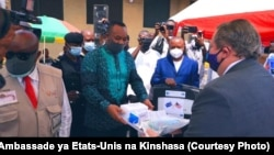 Ambassadeur ya Etats-Unis na RDC Mike Hummer azali kopesa lisungi na ministre ya Santé Dr. Eteni Longondo, Kinshasa, 16 mai 2020. (Facebook/Ambassade des Etats-Unis)