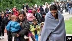Migrantes caminan hacia la estación de trenes en Dortmunt, Alemania.