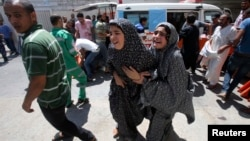 Palestinians react to what witnesses said was heavy Israeli shelling, at a hospital in Rafah in the southern Gaza Strip August 1, 2014.