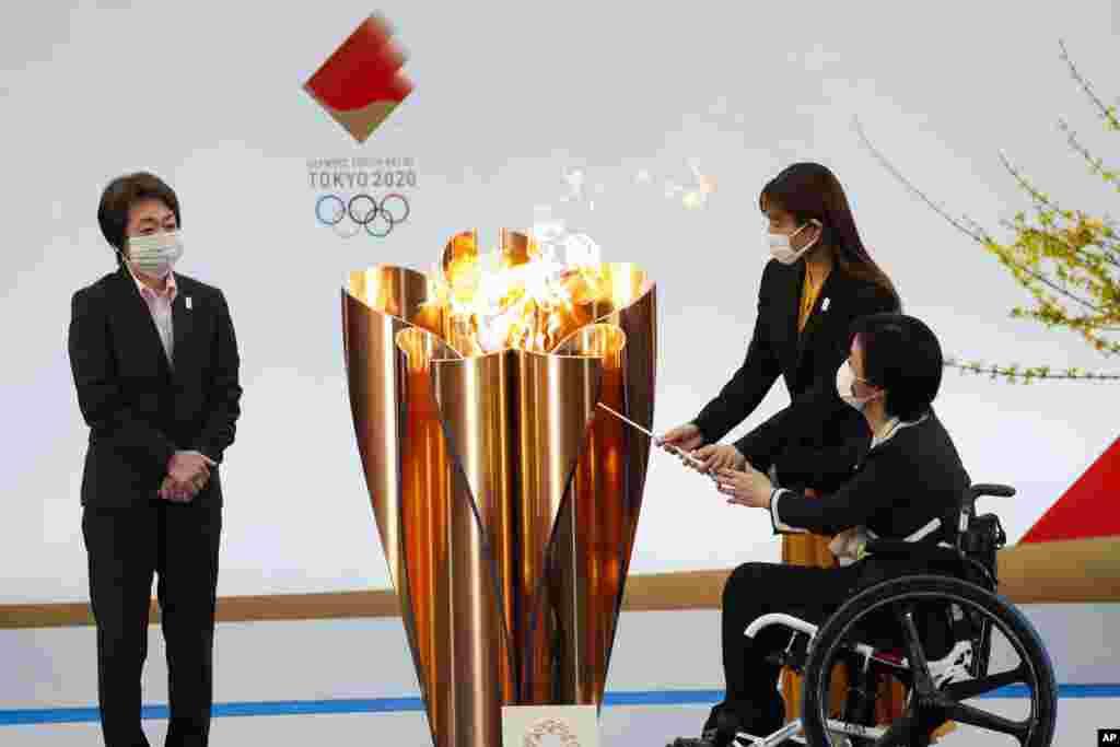 Tokyo 2020 President Seiko Hashimoto, left, watches Japanese actress Satomi Ishihara and Paralympian Aki Taguchi light the celebration cauldron on the first day of the Tokyo 2020 Olympic torch relay in Naraha, Fukushima prefecture, northeastern Japan.