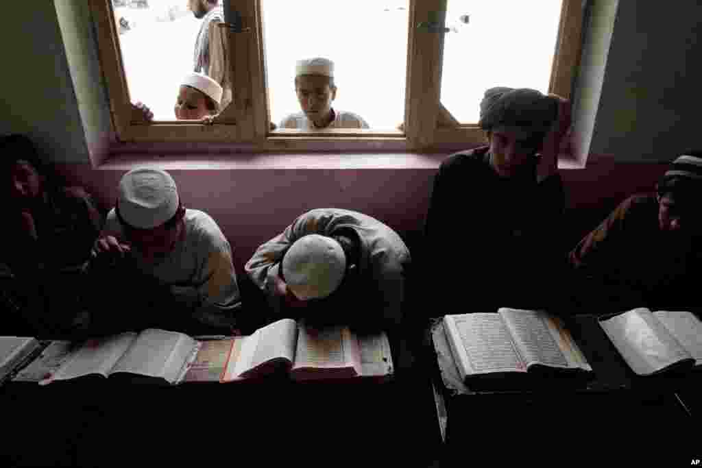 Boys read the Quran during the Muslim holy month of Ramadan at a mosque on the outskirts of Kabul, Afghanistan, July 16, 2013.