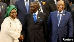 FILE: Chairperson of the African Union (AU) Commission Nkosazana Dlamini-Zuma (L) smiles as she is greeted by Zimbabwe's President Robert Mugabe next to South Africa's president Jacob Zuma ahead of the 25th African Union summit in Johannesburg, June 14, 2015.