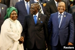 Chairperson of the African Union (AU) Commission Nkosazana Dlamini-Zuma (L) smiles as she is greeted by Zimbabwe's President Robert Mugabe next to South Africa's president Jacob Zuma ahead of the 25th African Union summit in Johannesburg, June 14, 2015.