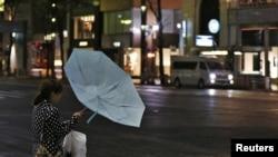 Seorang warga Tokyo di distrik perbelanjaan Ginza kesulitan membawa payungnya akibat tiupan angin kencang dampak topan Jelawat yang melanda Jepang (30/9).