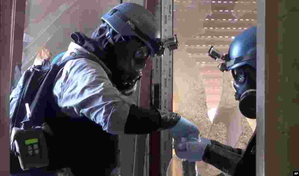 In this image taken from video obtained from the Shaam News Network, U.N. investigators gather potential evidence in a Damascus suburb, August 28, 2013.