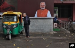 FILE - A man chats with an auto rickshaw driver standing next to a portrait of Indian Prime Minister Narendra Modi outside a public toilet in New Delhi, India, Feb. 14, 2019.