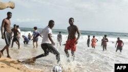 Des jeunes jouent au football devant d'autres se baignant dans la mer sur une plage de Grand-Bassam, en Côte d'Ivoire, le 28 mars 2021.