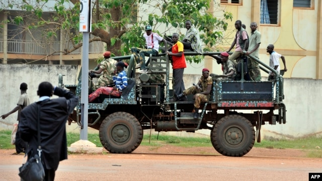 A man watches a truck with former Seleka coalition rebels drive by on Oct. 7, 2013 in Bangui, Central African Republic.