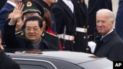 Chinese President Hu Jintao, accompanied by Vice President Joe Biden, waves during the arrival ceremony, Tuesday, Jan. 18, 2011, at Andrews Air Force Base, outside Washington.
