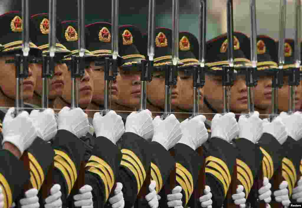 Members of the honor guard use a string to ensure that they are standing in a straight line outside the Great Hall of the People in Beijing, China.