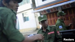 Armed soldiers from Burma's United Wa State Army shown riding a vehicle in neighboring China's border town of Mangka, September 3, 2009.