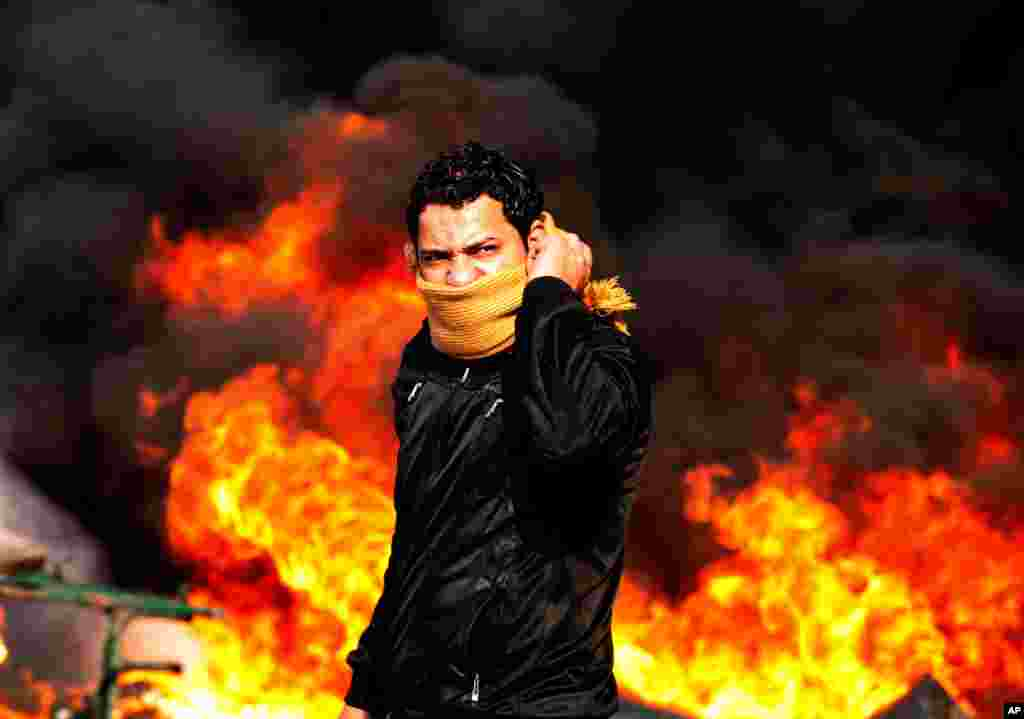 A protester stands in front of a burning barricade during a demonstration in Cairo, Egypt, Jan. 28, 2011. (Reuters)