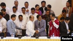 Myanmar President Thein Sein (front 3rd L) and Naing Han Tha (front 3rd R), a leader of the Nationwide Ceasefire Coordinating Team (NCCT), shake hands after signing a nationwide ceasefire draft agreement at the Myanmar Peace Center in Yangon, March 31, 2015.