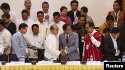 缅甸总统吴登盛(左三)和缅甸全国停火协调小组(NCCT)的领导人乃汉达(右三)在仰光签订全国性的停火协议草案后握手。(资料照片)