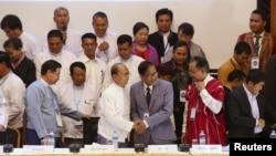Presiden Myanmar Thein Sein (ketiga dari kiri, di depan) dan Naing Han Tha (ketiga dari kanan, di depan), pemimpin Nationwide Ceasefire Coordinating Team (NCCT), berjabat tangan setelah menandatangani persetujuan gencatan senjata di Pusat Perdamaian Myanmar di Yangon, 31 Maret 2015.