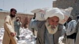 FILE - In this May 10, 2009 file photo, a man carries a sack of wheat distributed to poor displaced families, distributed by World Food Program in Kandahar, Afghanistan.