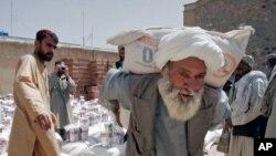 Pada foto yang diambil 10 Mei, 2009, tampak seorang pria memikul sekarung gandum yang didistribusikan oleh Badan Pangan PBB WFP untuk warga miskin di Kandahar, Afghanistan. (Foto:AP/Allauddin Khan)
