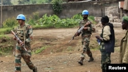 U.N. peacekeepers walk past rebel soldiers in Bunagana, July 7, 2012.
