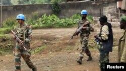 U.N. peacekeepers walk past rebel soldiers in Bunagana, July 7, 2012.
