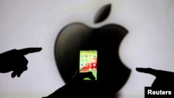 Men are silhouetted against a video screen with an Apple Inc logo as they pose with a Samsung Galaxy S3 smartphone, May 17, 2013.