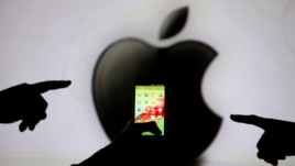 Pointing fingers are silhouetted against a video screen with an Apple Inc. logo as they pose with a Samsung Galaxy S3 smartphone, May 17, 2013.