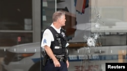 A Chicago Police officer inspects an Apple store that was vandalized, August 10, 2020.