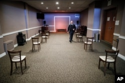 Pat Marmo, owner of Daniel J. Schaefer Funeral Home, walks through a viewing room set up to respect social distancing April 2, 2020, in the Brooklyn borough of New York.