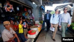 FILE - U.S. Secretary of State John Kerry (R) visits the village of Kien Vang along the Mekong River Delta, Vietnam, Dec. 15, 2013.