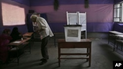 Egyptian man speaks to election workers during runoff of first-round parliamentary elections, Al-Haram in Giza, a neighboring city of Cairo, Oct. 27, 2015.