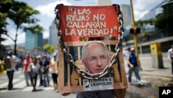 "Anti-government demonstrators holds a poster that reads in Spanish ""The jails won't shut the truth"" and the image of opposition leader arrested Antonio Ledezma during a protest against Venezuela's President Nicolas Maduro in Caracas, Venezuela, Aug. 12, 2017."