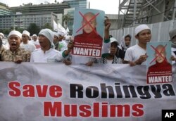 Indonesian Muslims hold defaced posters of Myanmar's radical Buddhist monk Ashin Wirathu during a protest demanding an end to the violence against ethnic Rohingyas in Rakhine State, outside the Embassy of Myanmar in Jakarta, Indonesia, May 27, 2015.