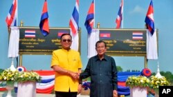 In this photo released by the Government Spokesman's Office, Thailand's Prime Minister Prayuth Chan-ocha (L) shakes hand with Cambodian's Prime Minister Hun Sen at the Thai-Cambodian border town of Aranyaprathet, Thailand, April 22, 2019.